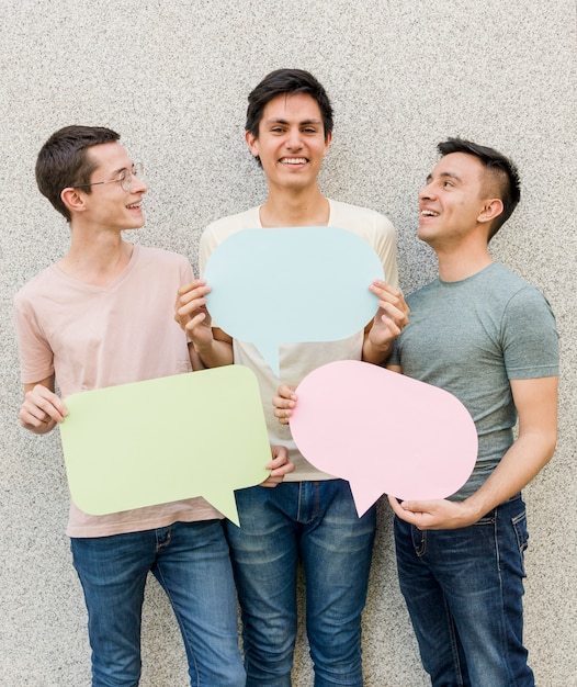 Group of young men holding speech bubbles Free Photo
