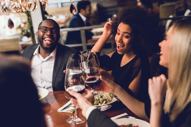 Group of young people drinking wine in a restaurant. Premium Photo