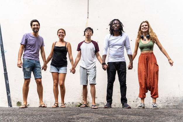 Group of young people from different ethnic groups holding hands next to a wall Premium Photo