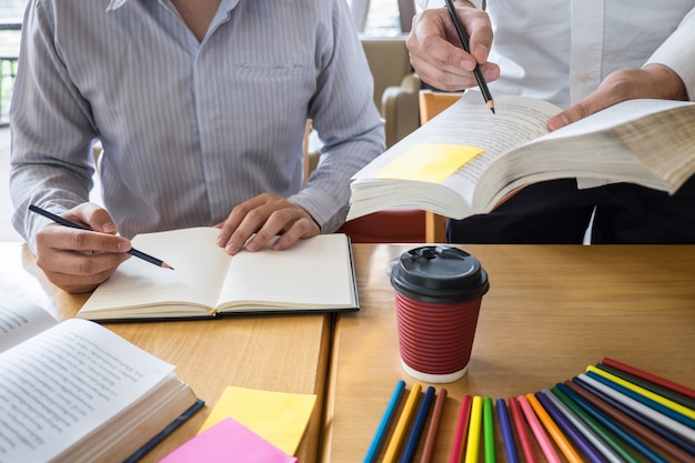 Group of young people learning studying new lesson to knowledge in library during helping teaching friend education prepare for exam, youth campus friendship teenager teens concept Premium Photo