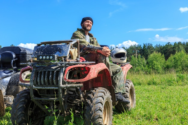 Group of young people riding atv on dirt track Premium Photo