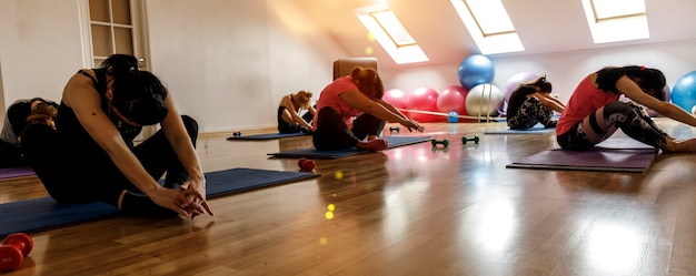 Group of young sporty attractive people practicing yoga lesson with instructor. Premium Photo