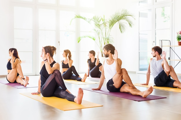 Group of young and sporty people doing matsyendrasana pose during yoga class in spacious bright studio Premium Photo
