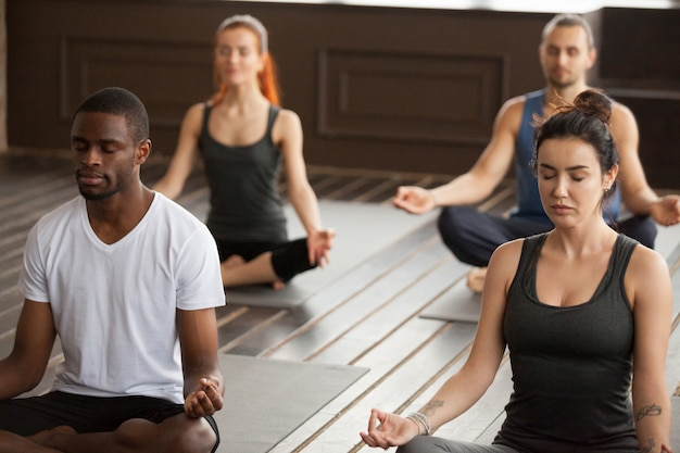Group of young sporty people meditating in easy seat pose Free Photo