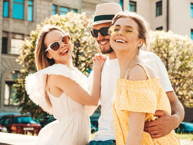 Group of young three stylish friends posing in the street. fashion man and two cute girls dressed in casual summer clothes. smiling models having fun in sunglasses.cheerful women and guy outdoors Free Photo