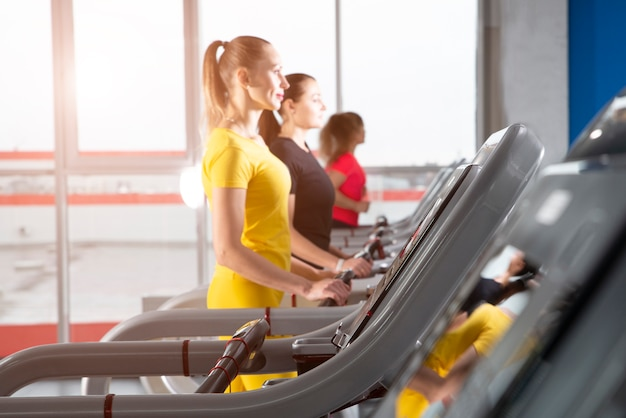 Group of young women running on treadmills in modern sport gym Premium Photo