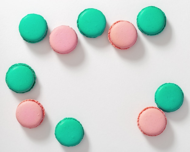 Groups of tasty macaroon biscuits of green and pink on white Premium Photo