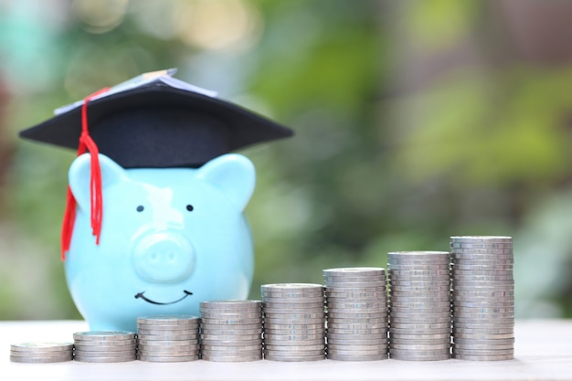 Growing stack of coins money with graduation hat on piggy Premium Photo