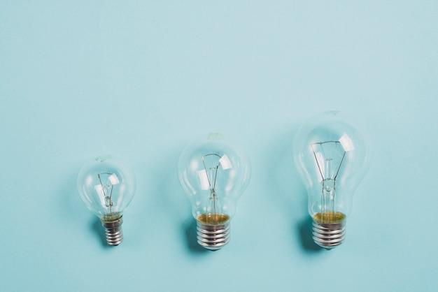 Выращивание прозрачной лампочки на синем фоне Бесплатные Фотографии