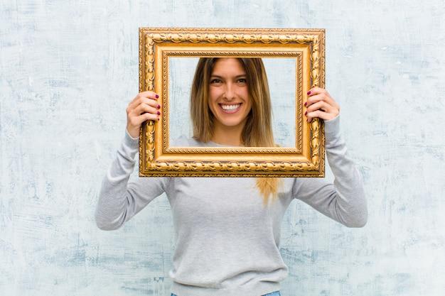 Молодая милая женщина с барочной рамкой против стены grunge Premium Фотографии