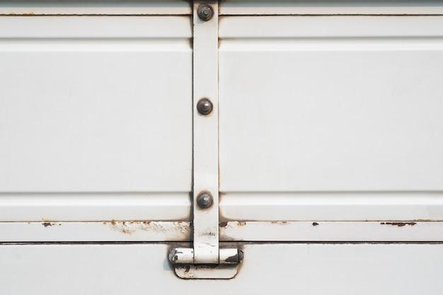 Старая белая тележка с предпосылкой ржавого, grunge металла белой краской и поверхностью. Premium Фотографии
