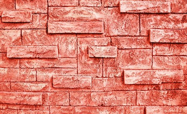 Тонизированная предпосылка grunge текстуры кирпичной стены цвета коралла. Premium Фотографии