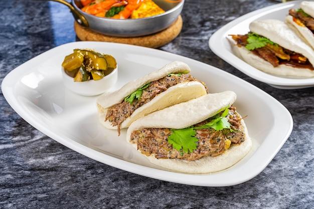 牛の頬とバオのビューを閉じます。グアバオ、白い皿に蒸しパン。大理石のテーブルで台湾の伝統的な料理gua bao。アジアンサンドイッチ蒸し。アジアのファーストフード Premium写真