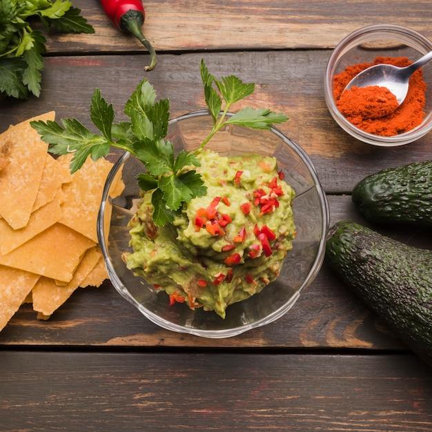 Guacamole among nachos and paprika with avocado Free Photo
