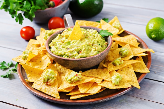 Guacamole avocado with nachos - traditional mexican snack Premium Photo