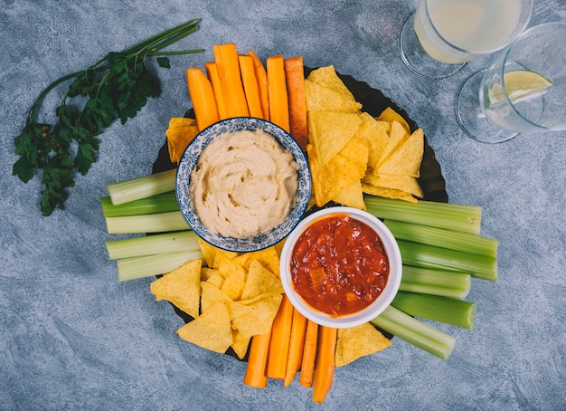 Guacamole and salsa sauce in bowl with carrot; celery stem; juice; coriander and tortilla chips over concrete background Free Photo