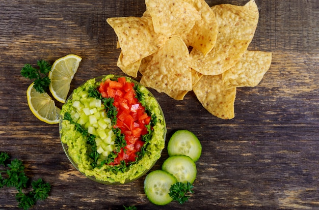 Guacamole with corn chips on rustic wooden table Premium Photo