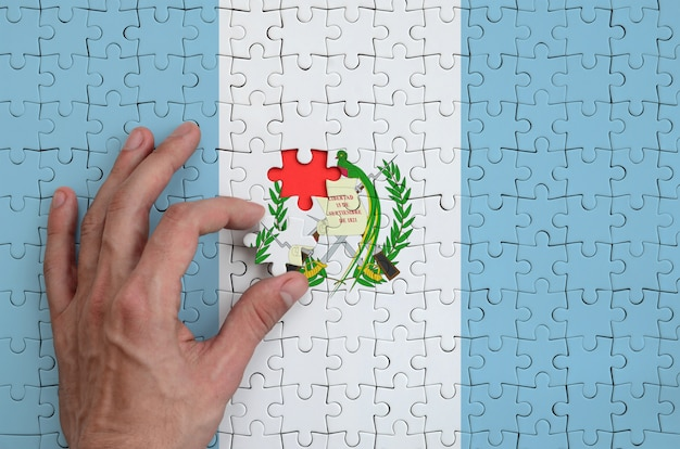 Guatemala flag is depicted on a puzzle, which the man's hand completes to fold Premium Photo