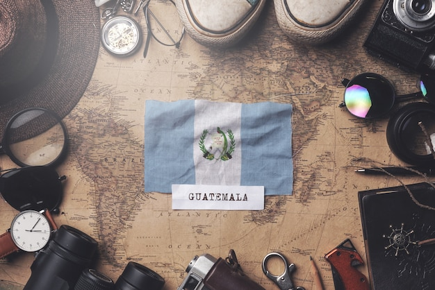 Guatemala flag between traveler's accessories on old vintage map. overhead shot Premium Photo