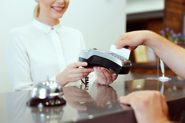 Guest at hotel reception paying with check during check-in Premium Photo