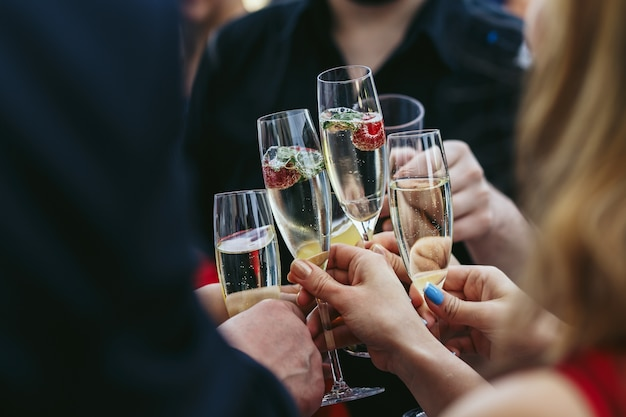 Guests clang glasses of champagne with delicious strawberries Free Photo