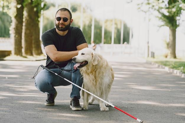 盲導犬が市内の盲人を助ける。ハンサムな盲目の男は、街でゴールデン・リトリーバーと残りを持っています。 無料写真