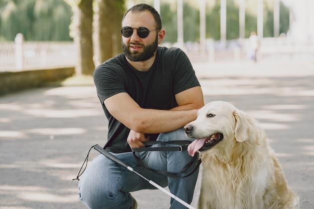 Собака-поводырь помогает слепому в городе. красивый слепой парень отдыхает с золотистым ретривером в городе. Бесплатные Фотографии