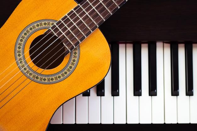 Guitar on piano. classical music instrument. Premium Photo