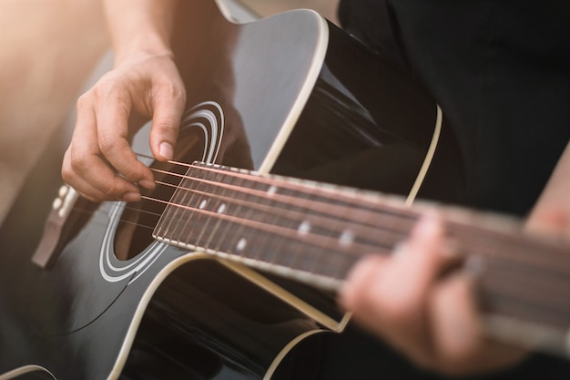 Guitar player playing acoustic guitar, close up Premium Photo