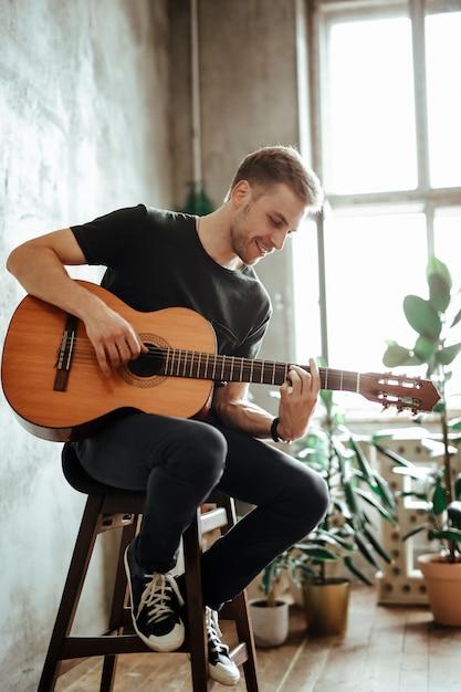 Гитарист человек играет на гитаре у себя дома Бесплатные Фотографии