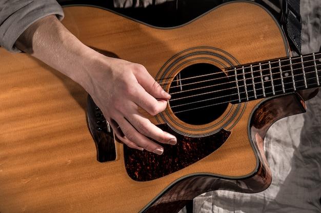 ギタリスト、音楽。若い男が分離された黒のアコースティックギターを弾く 無料写真