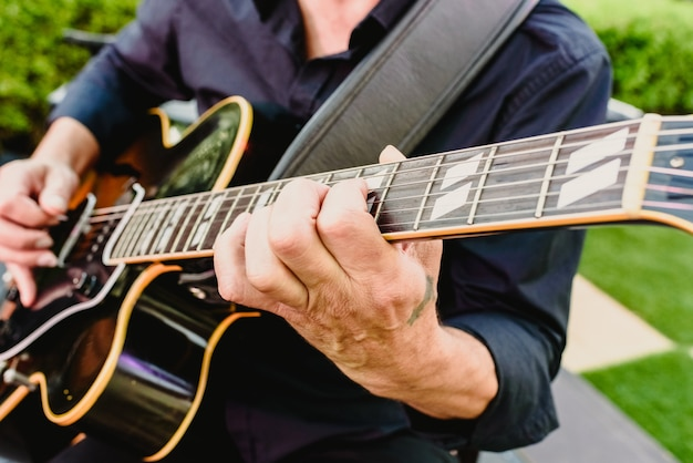 Guitarist playing his guitar outdoors Premium Photo