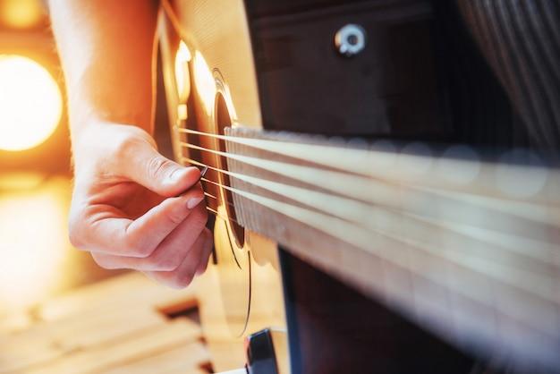 Guitarist plays guitar on wooden background Premium Photo
