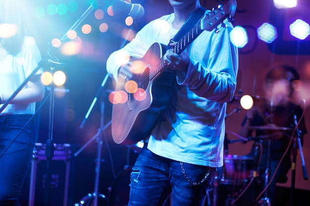 Guitarist on stage with lighting for blackground. guitar player, soft and blur concept. Premium Photo