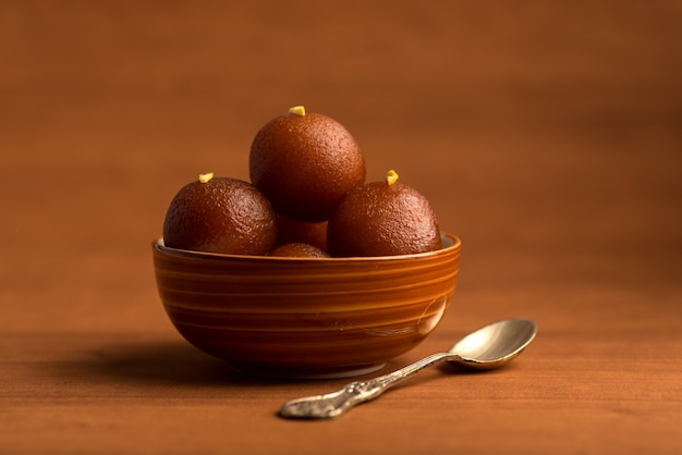 Gulab jamun in bowl on wooden table. indian dessert or sweet dish. Premium Photo