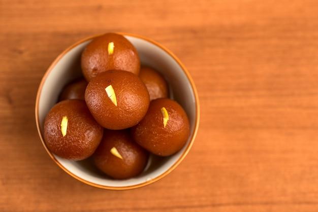 木製のボウルにgulab jamun。インドのデザートまたは甘い料理。 Premium写真