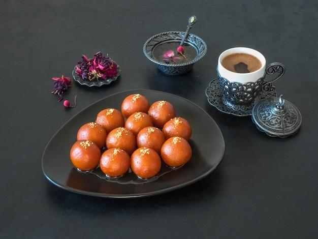 Gulab jamun-黒いテーブルに伝統的なインドのお菓子 Premium写真