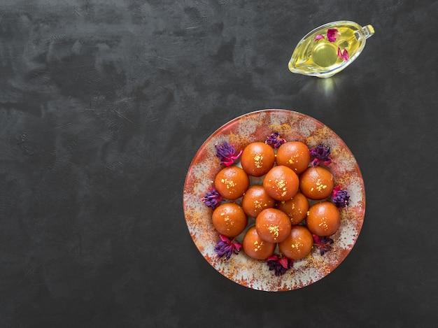 黒いテーブルにインドの伝統的な甘いgulab jamun Premium写真