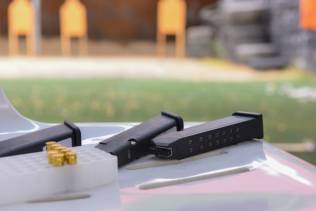 Gun bullets  and magazine shooting accessories on the table Premium Photo