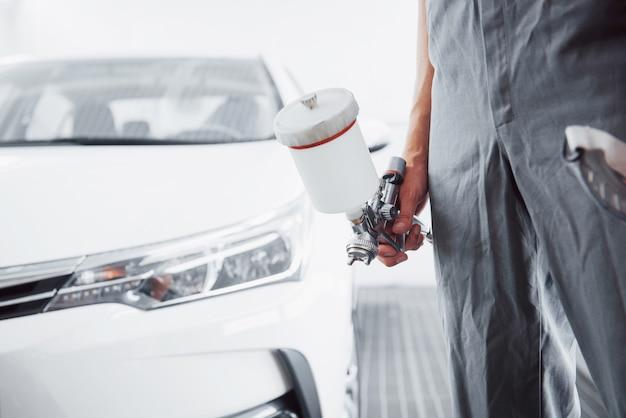 자동차를 페인트하는 남자의 손에 페인트 총 프리미엄 사진