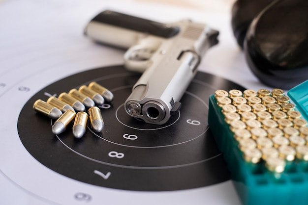 Guns with ammunition on paper target Photo | Premium Download
