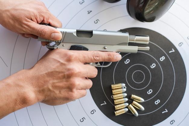 Guns with ammunition on paper target Premium Photo