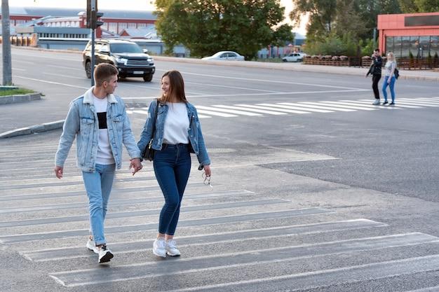 男と女は手をつないで、交差点に沿って道路を横断します。路上でのデート Premium写真