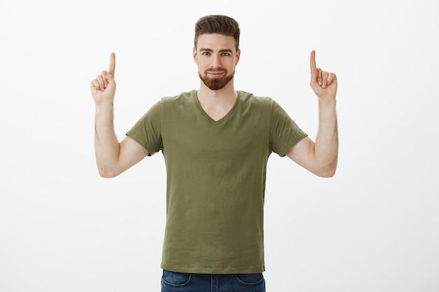 商品をチェックアウトする必要があることを確信し、人差し指をコピースペースに向けて自信を持って笑いながら、白い壁越しに試してみるように強くて自信を持って励ましてください。 無料写真