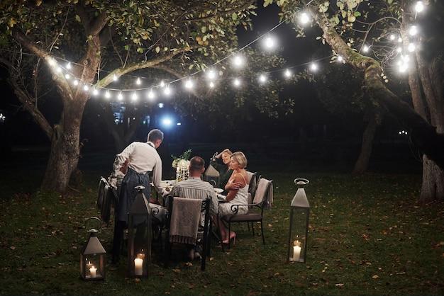 男は命令をもたらしました。友達は夕方に集まります。外の素敵なレストラン 無料写真