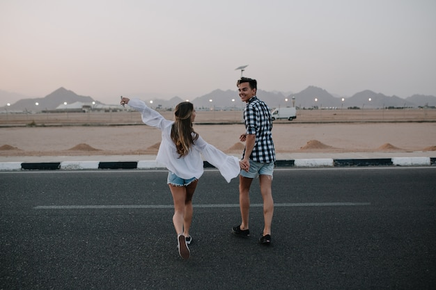 Guy in denim shorts and long-haired woman in trendy blouse running across the road and enjoys mountain view. laughing young couple holding hands walking on highway and having fun outside in summer Free Photo