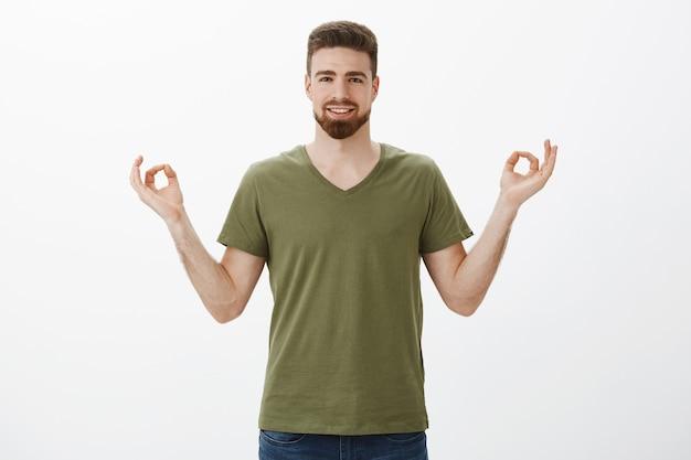 Парень чувствует себя спокойно и расслабленно, без стресса благодаря новым таблеткам, широко улыбается и отпускает, держась за руки в дзен, улыбающийся жест лотоса, довольный медитацией и практикой йоги над белой стеной Бесплатные Фотографии