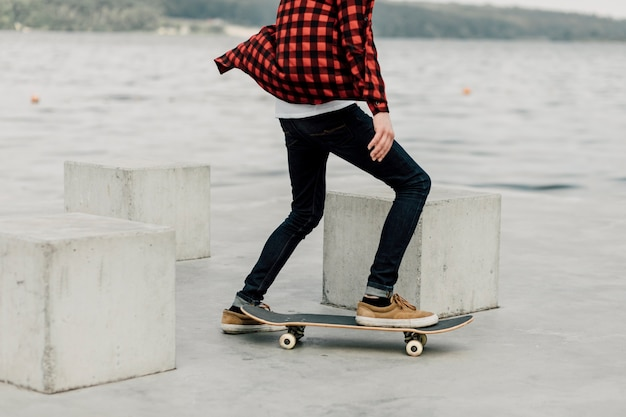 Guy in flannel skateboarding by the lake Free Photo
