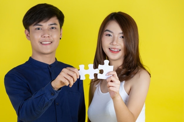 The guy and the girl are holding jigsaw pieces on yellow wall Free Photo
