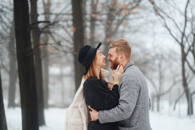 The guy and the girl are resting in the winter forest. Free Photo
